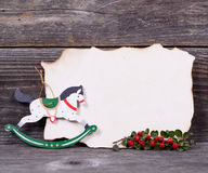 Christmas background with empty paper and wooden horse decoratio Stock Photos