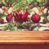 Christmas background with empty wooden deck table over Christmas tree decorations. Christmas background with empty wooden deck table over retro Christmas tree stock photography
