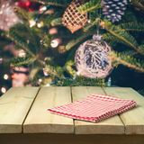 Christmas background with empty wooden table and tablecloth over Christmas tree decorations. Christmas background with empty wooden table and tablecloth over royalty free stock photography