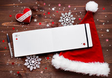 Christmas background with felt heart, red Santa's hat and notepad. Stock Photography