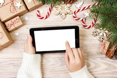 Christmas background: female hands uses opened tablet with copy space on rustic wooden table covered with Christmas decoration. to stock image