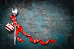 Christmas background for festive dinner with fork and red decoration on vintage background. Top view Stock Photo