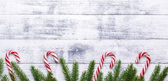 Christmas background. Fir branches, candy cane and gifts on a light wooden background. Cranberries, spices stock image