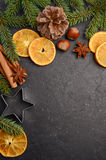 Christmas background with fir branches, cones, nuts and slices of dried orange. Royalty Free Stock Photo