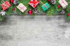 Christmas background with fir branches, decorations, gift boxes and pine cones on rustic wooden table royalty free stock photo
