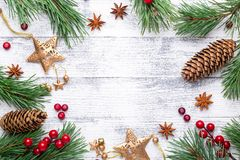Christmas background. Fir branches and gifts on a light wooden background. Cranberries, spices, holly berries. stock image