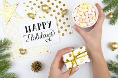 Christmas background with fir branches, golden decorations. Female hands holding gift box. Happy holidays trandy Stock Image