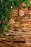 Christmas background. Fir branches, red balls, gingerbread on the old brown boards. Rustic style.  Copy space Royalty Free Stock Image