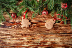 Christmas background. Fir branches, red balls, gingerbread on the old brown boards. Rustic style. Copy space stock images