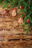 Christmas background. Fir branches, red balls, gingerbread on the old brown boards. Rustic style.  Copy space Stock Image