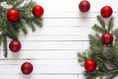 Christmas background with fir branches and red decorations on white wooden boards. Space for text. royalty free stock photography