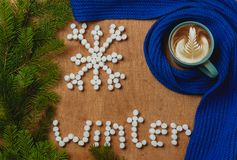 Christmas background with fir, word winter, snowflake, scarf, cup of coffee Stock Photos