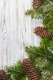 Christmas background. Fir tree branch pine cones at wooden table. Flat lay, space for text royalty free stock images