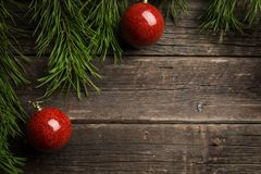 Christmas background. Fir tree branch red Christmas ball decorations at wooden table. royalty free stock photography