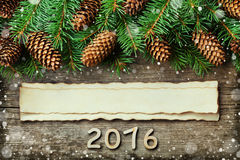 Christmas background of fir tree and conifer cone on old vintage wooden board, fantastic snow effect, wooden numbers of New year a Stock Photography