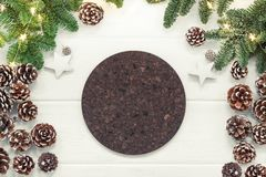 Christmas background with fir tree and empty round cork coaster. On white wooden board Royalty Free Stock Images