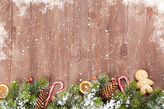 Christmas background with fir tree and food decor. Christmas wooden background with snow fir tree and food decor. View with copy space Royalty Free Stock Images