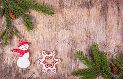 Christmas background with fir tree and gingerbread on a wooden background. Painted Gingerbread Cakes. Snowman and snowflake Royalty Free Stock Photos