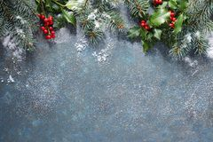 Christmas background with fir tree and holly berry, covered in s. Christmas background with fir tree and holly berry on a blue stone background covered in snow royalty free stock photo