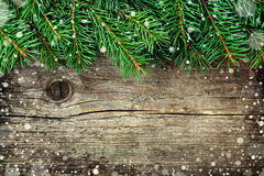 Christmas background of fir tree on old vintage wooden board, fantastic snow effect, copy space for text Royalty Free Stock Photos