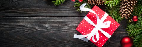 Christmas background with fir tree and red box present at dark royalty free stock photo