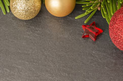 Christmas background with firtree, baubles and stars on slate close up Royalty Free Stock Photo