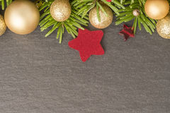 Christmas background with firtree, baubles and stars on slate Royalty Free Stock Photo