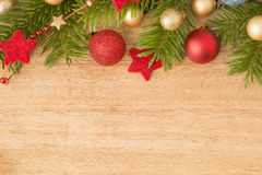 Christmas background with firtree, baubles and stars on wood Royalty Free Stock Photos