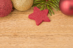Christmas background with firtree, baubles and stars on wood Royalty Free Stock Photo