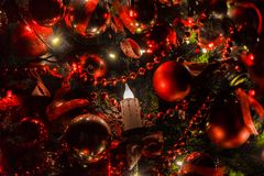Christmas background with flashing garland on the tree. Classic green new year tree with flashing garland in the dark room. Christmas interior background Royalty Free Stock Photography