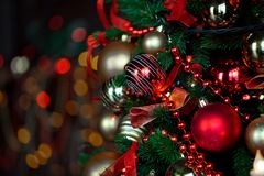 Christmas background with flashing garland on the tree. Classic green new year tree with flashing garland in the dark room. Christmas interior background Royalty Free Stock Images