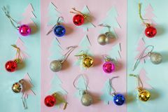 Christmas background. Flat lay. Christmas balls and paper fir-trees. On colored paper background royalty free stock photography