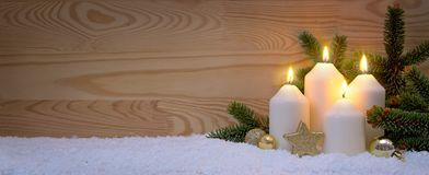 Four burning Advent candles and white snow. Fourth Advent. Christmas background with four white advent candles and golden decoration.Fourth Advent Stock Photos