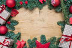 Christmas background frame with fir branches and other decorations presents red stars and bulbs with copy space on wooden table stock photo