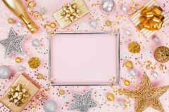 Christmas background with frame, gift or present box, champagne, confetti and holiday decorations on pink pastel table top view. stock image