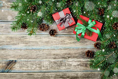 Christmas background with gift box, fir branch and conifer cone on wooden rustic board, festive snow effect, Christmas frame Royalty Free Stock Images