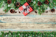 Christmas background with gift box, fir branch and conifer cone on wooden rustic board, festive snow effect, Christmas frame Stock Image