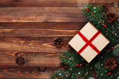 Christmas background of gift box, fir tree and conifer cone on rustic wooden table top view. Snow effect. Flat lay. Stock Images
