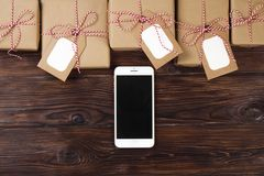 Smart phone with christmas presents on wooden background top view. Online holiday shopping concept. Flat lay, text space. Internet. Christmas background with stock photography