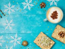 Christmas background with gift boxes, coffee cup. And snowflakes on wooden table. View from above. Flat lay Royalty Free Stock Image