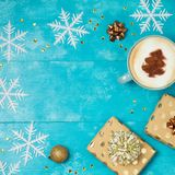 Christmas background with gift boxes, coffee cup. And snowflakes on wooden table. View from above. Flat lay Royalty Free Stock Photos