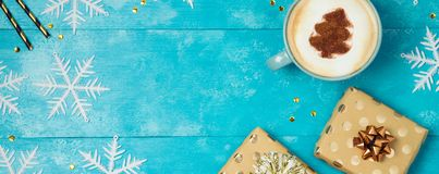 Christmas background with gift boxes, coffee cup. And snowflakes on wooden table. View from above. Flat lay stock photography