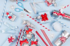 Christmas background - gift boxes in red, blue and silver metallic color with ribbons, decorations, scissors, straws as pattern. royalty free stock photos