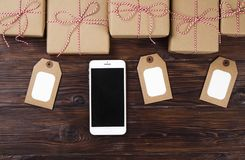 Smart phone with christmas presents on wooden background top view. Online holiday shopping concept. Flat lay, text space. Internet. Christmas background with stock photo