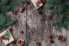 Christmas background with Christmas gift, pine cones, red decorations on wooden background with Fir branches royalty free stock photography