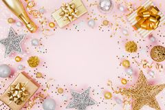 Christmas background with gift or present box, champagne, confetti and holiday decorations on pink pastel table top view. Flat lay stock photos
