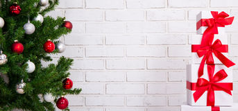 Christmas background - gifts and christmas tree over brick wall Royalty Free Stock Images