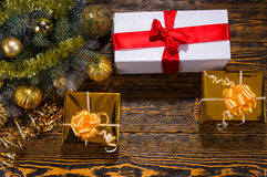 Christmas background with gifts and decorations. Christmas background with decorative gifts tied with ribbon and bows and golden bauble decorations arranged on a Royalty Free Stock Photos