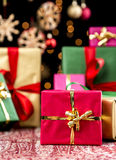 Christmas Background with Gifts and Glitters. Crimson red Xmas gift with golden bow in focus. Behind, the blurry shapes of green, magenta and golden presents Royalty Free Stock Image
