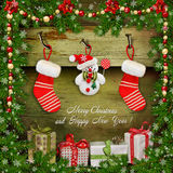 Christmas background with gifts, snowman, sock, pine branches. Pine branches, gifts, socks, Christmas decorations on a green wooden background Royalty Free Stock Image